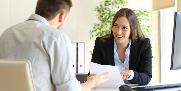 Woman in business suit smiling at man with paperwork in her hand