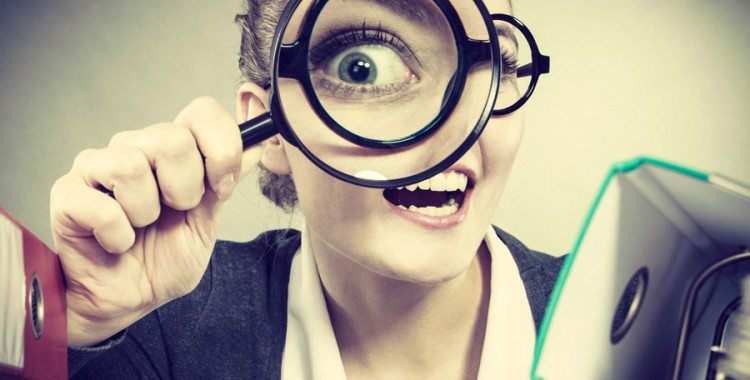 Business Woman smiling looking through magnifying glass