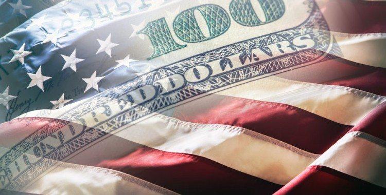 American 100 dollar bill fading over American flag