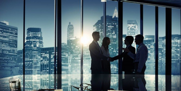 Business people silhouettes at office at night with dark cityscape in background