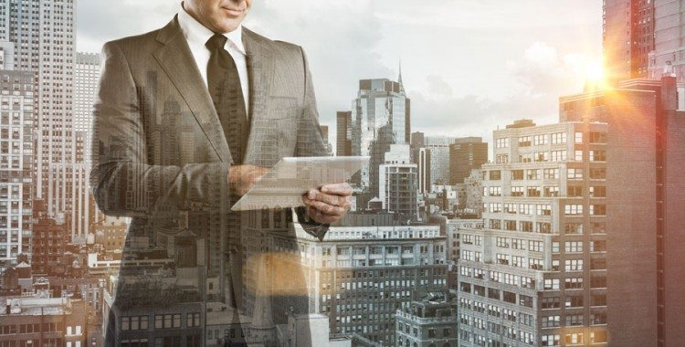 Business Man on tablet overlayed over cityscape