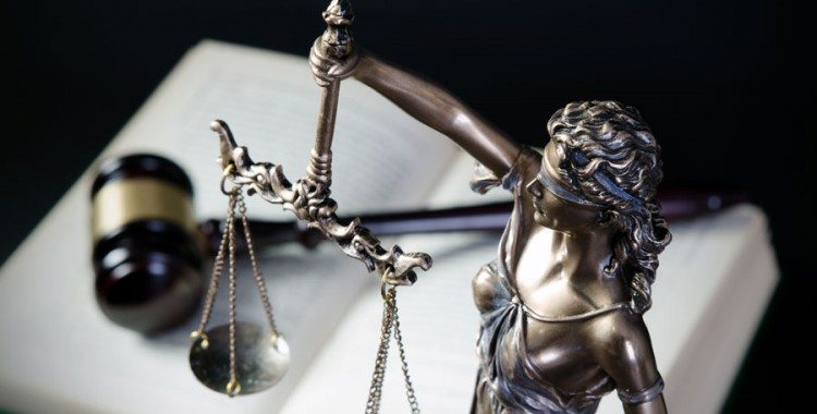 Lady Justice statue over gavel and open book