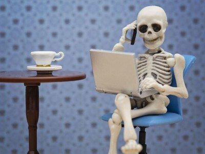 Skeleton on phone and laptop