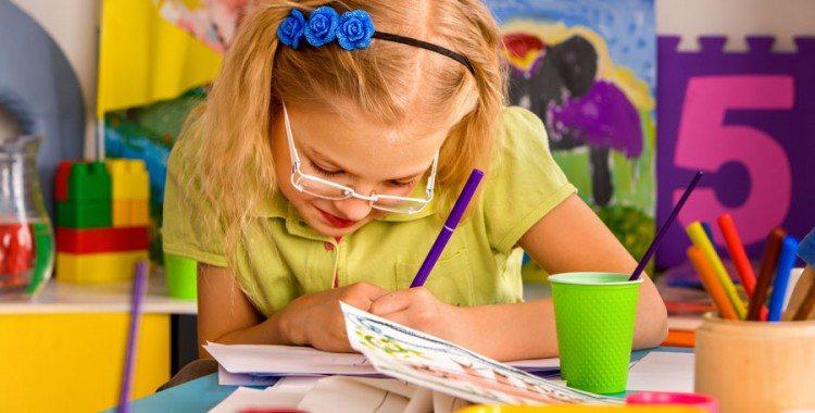 Little girl in school art room making crafts
