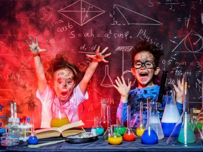 Two excited kids in science lab with test tubes exploding colors on them