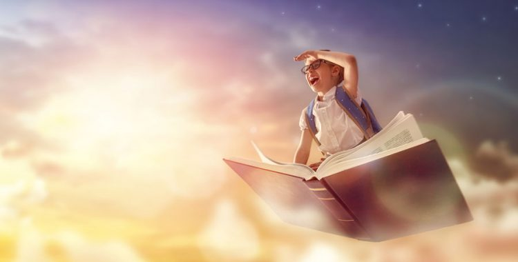 Young smiling school kid riding a book through a cloudy sky