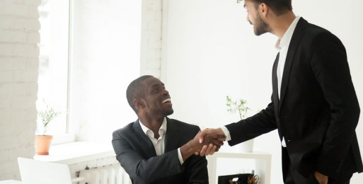 Standing business man shaking another business man's hand who's sitting down in an office setting