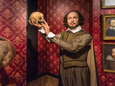 Man in classical costume holding up a skull