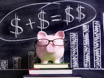 Piggy bank with glasses on top of books in front of chalk board with graph of dollar signs and increase in meters