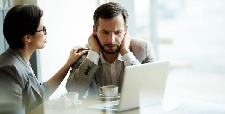 Man looking at computer stressed with woman talking to him