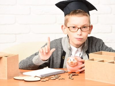 Boy with glasses and graduation hat holding piggy bank and one finger up