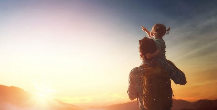 Man with daughter on his shoulder pointing at sunset