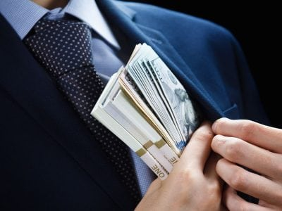 Business Man sneakily hiding wad of cash in suit jacket