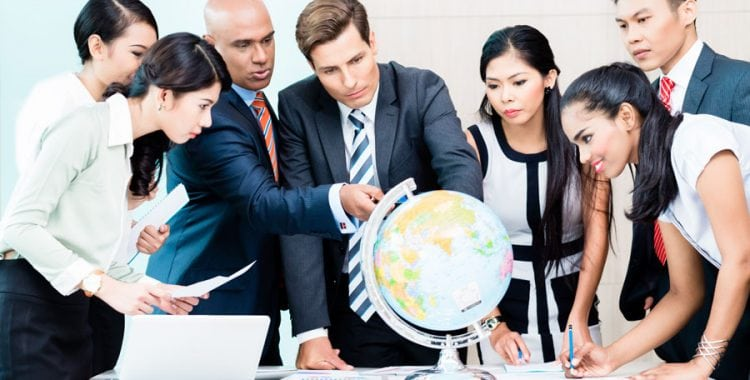 Multiple Business People surrounding and pointing at globe