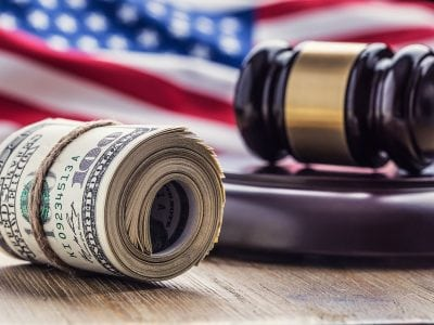 Roll of American dollars in front of Gavel and American Flag