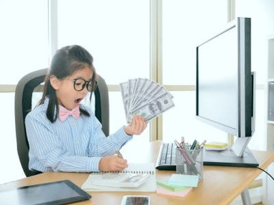 Young girl holding dollars and stressfully writing in notepad