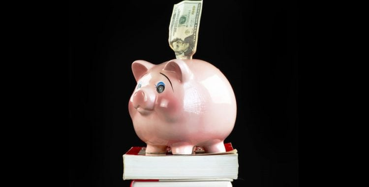 Piggy bank on top of books with dollar sticking out of top