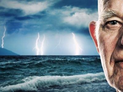 Half of man's face in front of ocean storm