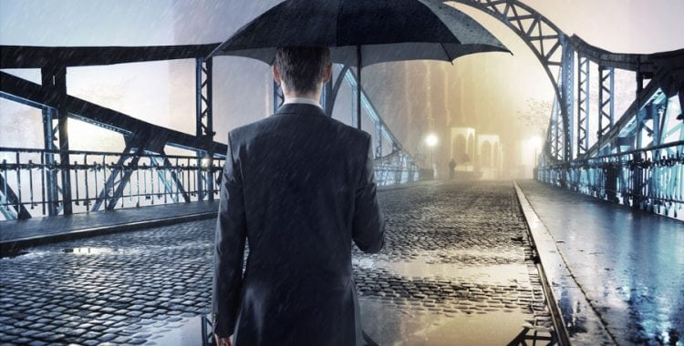 Business Man holding Umbrella in the rain looking towards a brighter future