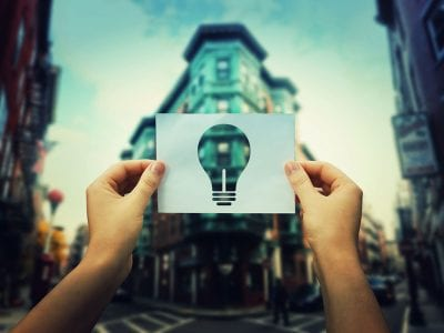 Hands in foreground holding up paper with light bulb shape cut out in front of building