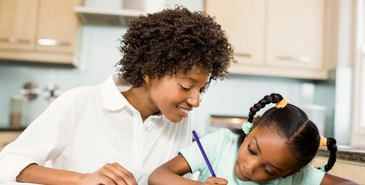 Parent helping young daughter with homework