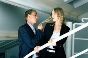 Business man touching business woman's hair in office stairs