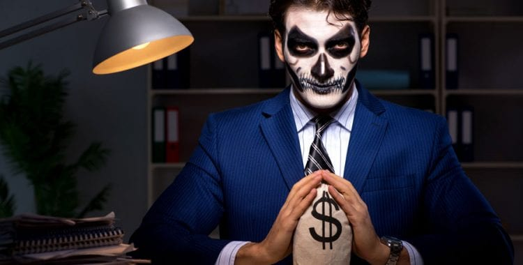 Business Man with skeleton face paint in dark office with bag of money
