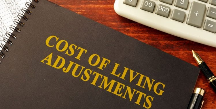 Cost of Living Adjustments book next to calculator