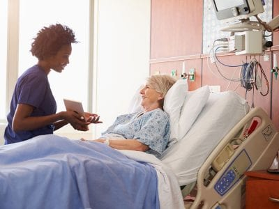 Nurse and elderly woman in hospital bed smiling