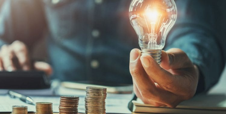 Man holding light bulb next to coins