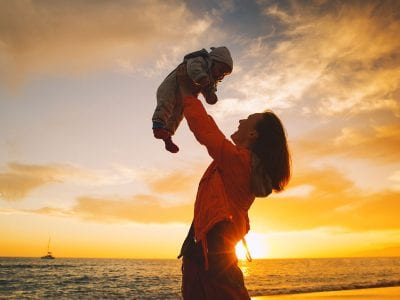 Mother holding baby over beach sunset