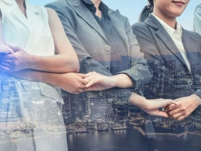 Business People holding hands over city overlay