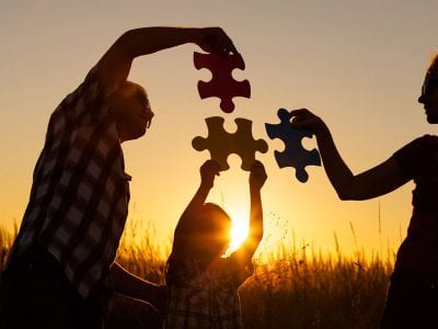 Family holding puzzle pieces in front of sunset