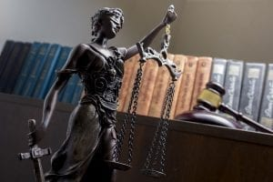 lady justice statue in front of books