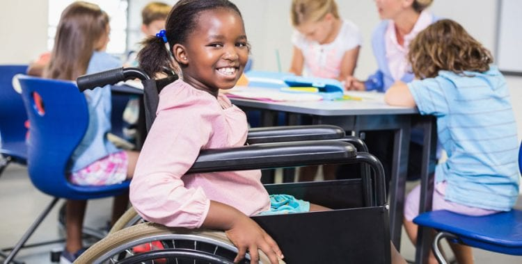 smiling girl in wheelchair at school