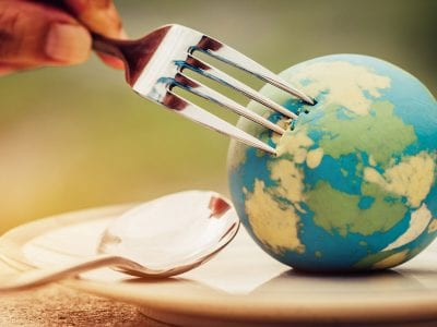 fork puncturing small globe on plate