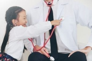 young girl using stethoscope on doctor