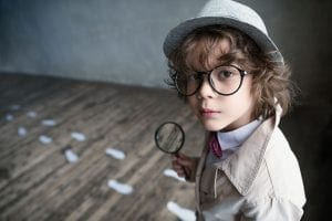 Child detective with magnifying glass and footprints on the ground