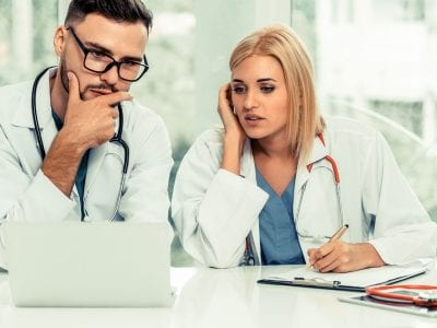 male and female doctor looking at laptop screen perplexed