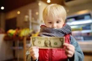 Blonde child holding a dollar bill