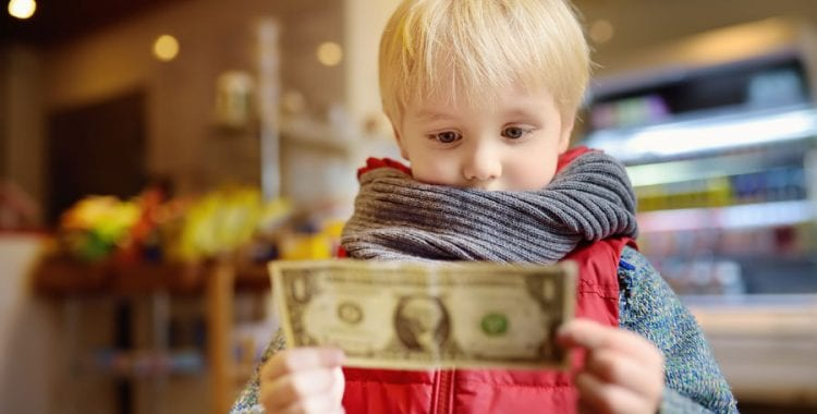 Blonde child holding a dollar bill