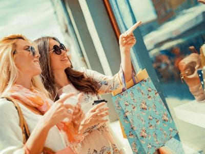 Women with shopping bags looking into store