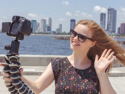 Girl waving into camera on selfie stick in front of city skyline