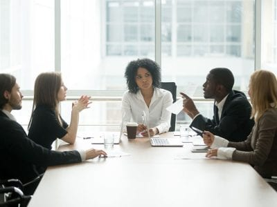 Business people arguing in meeting with frustrated business woman in the center