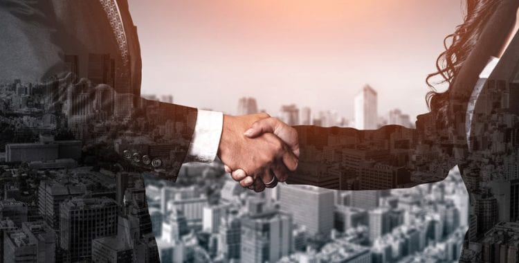Business People Shaking Hands in front of cityscape