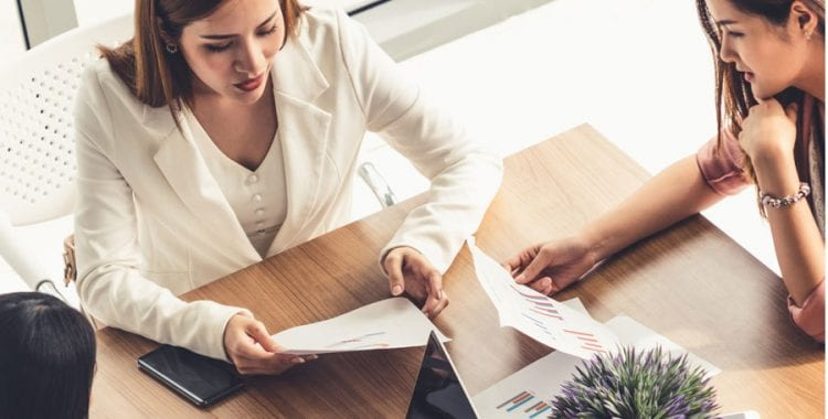 Woman sifting through papers in meeting