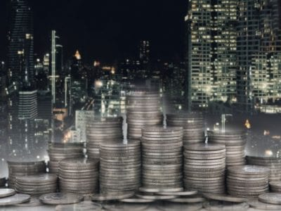 Coins stacked up in foreground, night city in background