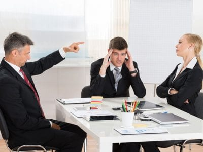 Business people arguing in meeting with frustrated business man in the center