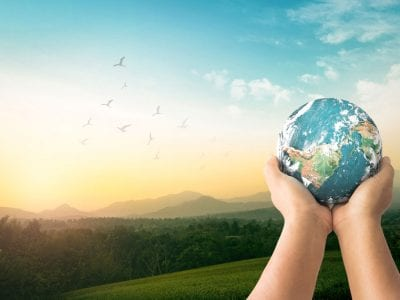 Hands holding up planet earth with landscape background